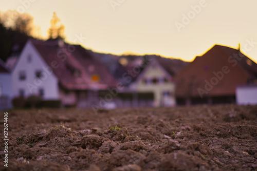 Photo  Acker im Frühjahr mit unscharfen Häusern im Hintergrund