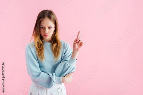 Fototapeta  sad teenage girl pointing with finger isolated on pink