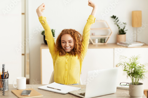 Creative Designer Stretching In Front Of Laptop Computer