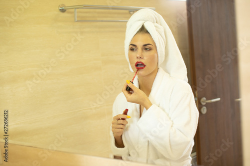 Photo Young woman applying lipstick looking at mirror