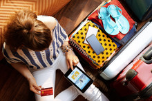 Young Woman Book Flight On Tablet PC Near Open Travel Suitcase