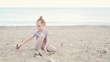 Baby blonde girl playing on the beach on the sand in the summer by the sea ocean, slow motion, close-up