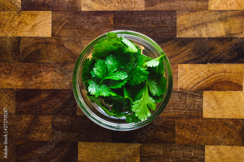 Glass Bowl of Cilantro Leaves on Butcher Block