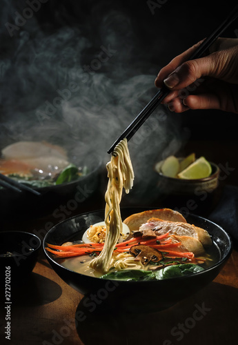 Photo  Hand with chopsticks takes noodles of ramen soup