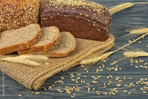 Photo  Rye bread and ears of rye on wooden table