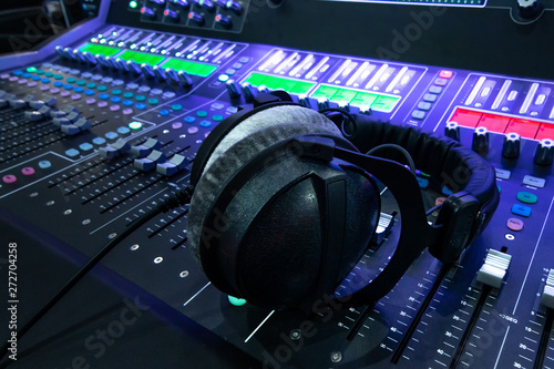 Fototapety, obrazy: Professional audio studio sound mixer console board panel with recording , headphone and adjusting knobs,TV equipment. Blue tone and close-up image with flare light effect.