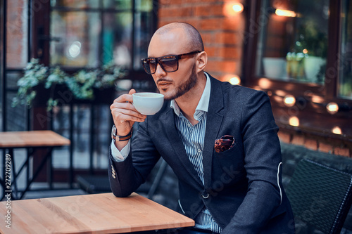 Photographie Pensive groomed man is enjoying coffee while sitting outside at cafe on his own break