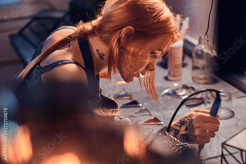 Obraz Beautiful diligent woman is doing soldering at her own artisan lamp studio. - fototapety do salonu