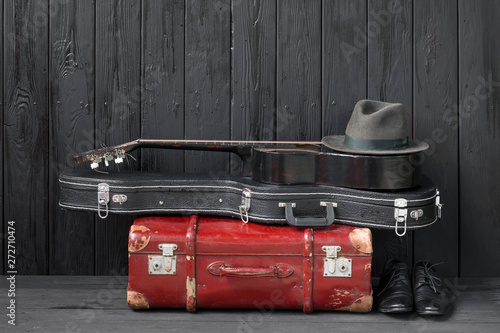 Fotografie, Tablou black guitar and a suitcase against a black wooden background