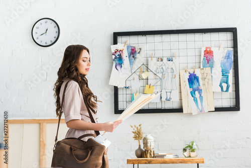 Fotografija  attractive young designer standing with bag near fashion sketches