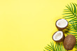canvas print picture Palm leaves and coconut on yellow top view.