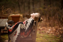 Side View Of Girl With Eyes Closed Wrapped In Blanket Relaxing On Bench At Forest