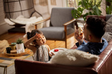 Cute Daughter Looking At Father Eating Sandwich On Sofa At Home