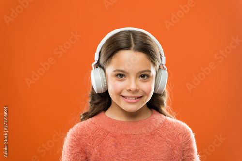 Music produces pleasure. Perfect sound stereo headphones. Girl cute little child wear headphones listen music. Kid listen music orange background. Recommended music based on initial interest - 272716684