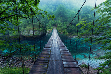 Fototapeta Mosty Wooden bridge across crystal clear river deep in nature