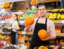Seller With Pumpkin In Supermarket
