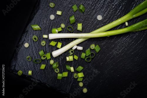 Poster de jardin Route Organic Green Onion Scallions arranged on black natural stone background. Allium onion species.