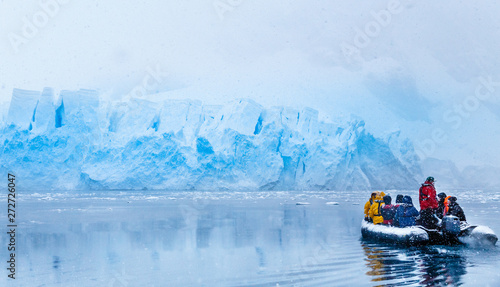Foto auf Gartenposter Antarktika Snowfall over the boat with frozen tourists driving towards the huge blue glacier wall in the background, near Almirante Brown, Antarctic peninsula