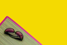 Sunglasses On A Wicker Bast Beach Mat With Pink Edging On A Yellow Background. Hot Summer And Beach Theme. Copy Space.