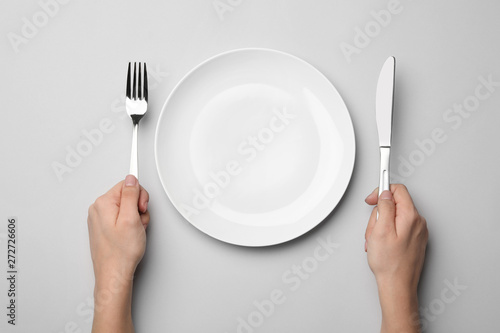 Tela Woman with fork, knife and empty plate on grey background, top view
