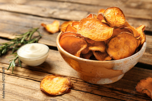 Foto Delicious sweet potato chips in bowl, rosemary and sauce on table