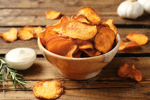 Fototapeta Delicious sweet potato chips in bowl, rosemary and sauce on table obraz