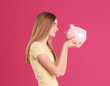 canvas print picture - Teen girl with piggy bank on color background