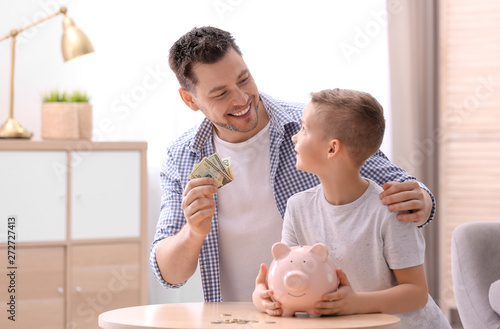 Fototapeta Family with piggy bank and money at home
