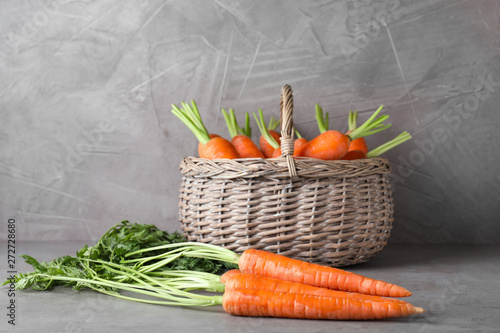 Photo Basket with fresh carrots on grey background