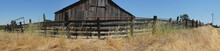 Old Wooden Barn Sitting Behind An Old Wooden Fence