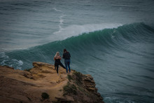 People Standing On A Rock Watc...