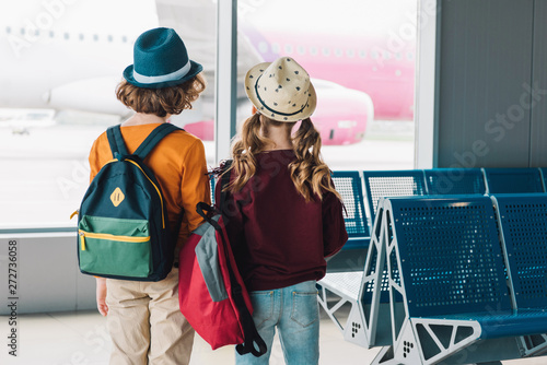 obraz dibond back view of preteen kids with backpacks in waiting hall