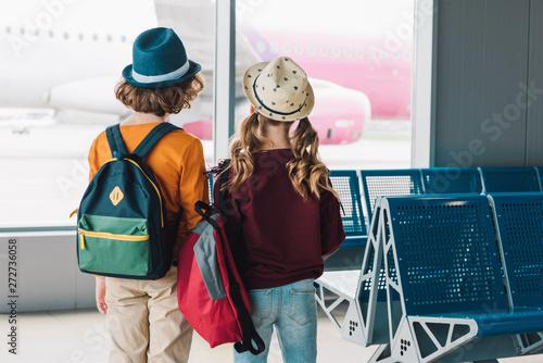 fototapeta na lodówkę back view of preteen kids with backpacks in waiting hall