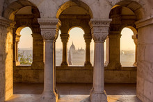 Aerial View Of The Parliament Of Hungary Through Gothic Windows Of Fisherman's Bastion (Halaszbastya) At Sunrise With Beautiful Sky And Clouds , Budapest, Hungary