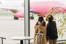 Two Kids Standing Near Table And Plant And Looking On Plane