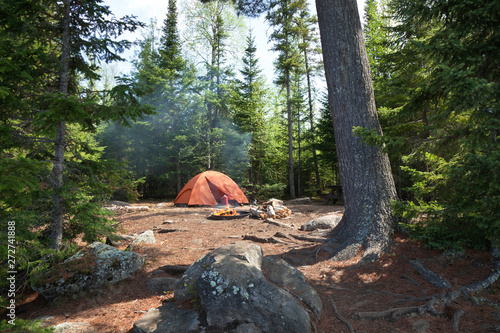 Obraz Campsite with orange tent and fire in the northern Minnesota wilderness - fototapety do salonu