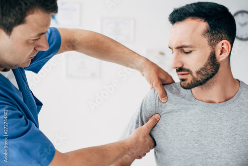 Fototapeta Selective focus of patient sitting on couch and doctor massaging patient shoulder in massage cabinet at clinic obraz