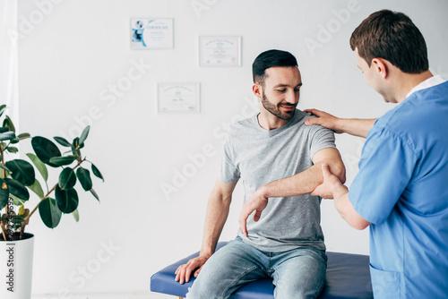 Vászonkép Selective focus of chiropractor examining patient shoulder in massage cabinet at