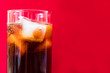 A glass of cola with ice on a red background. Concept for non-alcoholic cool drinks. Close-up..Copy space