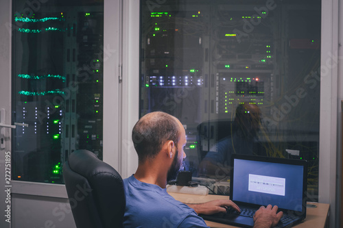 A programmer with a laptop sits in front of the glass wall of the server room Fototapete