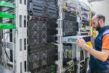 System Administrator Installs A New Server In A Modern Data Center. Engineer Replaces The Computer Equipment In The Cabinet. A Technician Repairs The Central Router. A Man Works In A Server Room.