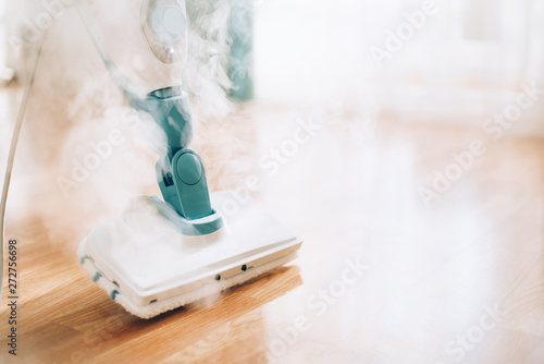 Fototapeta Steam cleaner mop cleaining floor. Banner with copy space. Cleaning service concept obraz