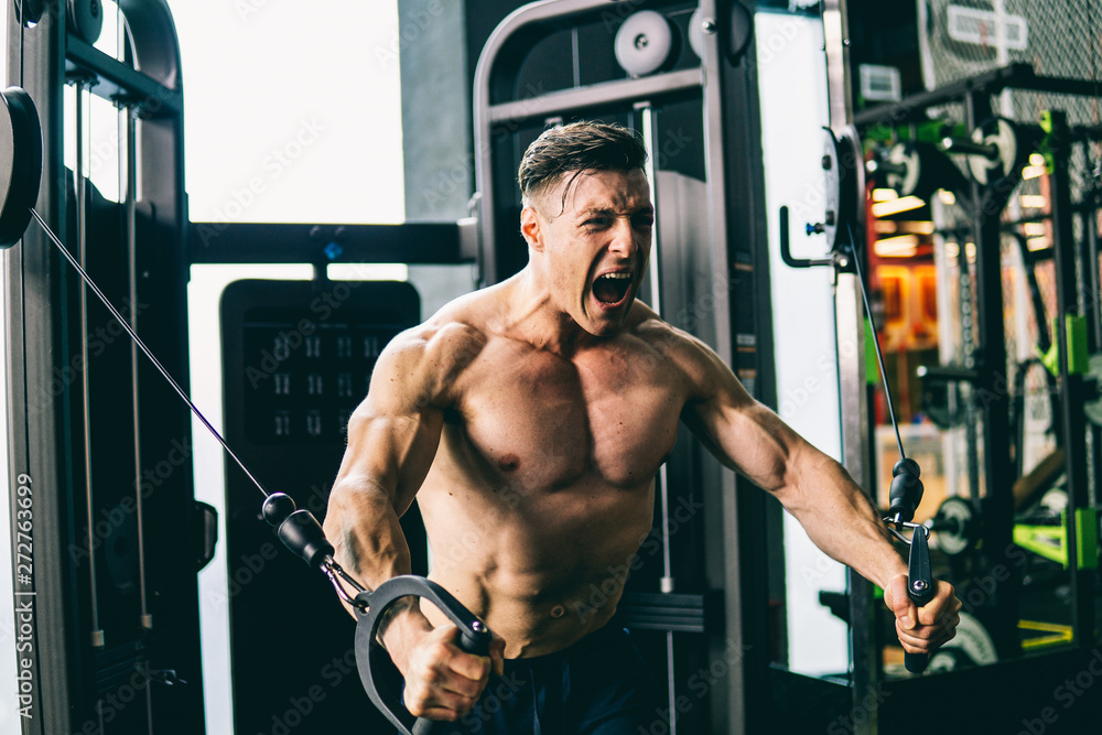 Fototapety, obrazy: Muscular man in gym training pumping up chest muscles with flying machine