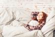 canvas print picture - portrait einer jungen frau mit sommersprossen und roten haaren zuhause beim erholen auf der couch