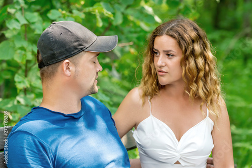 Young couple arguing on a bench in the summer park. Problems in relationship