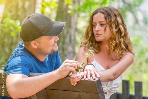 Сouple quarreled while sitting on bench in park. A man gives flowers to a woman as a sign of reconciliation. Problems in relationship