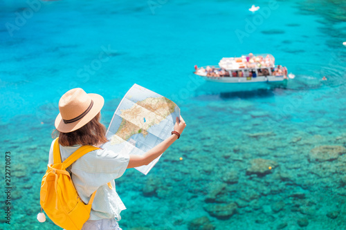 Photo  Cheerful girl with a map exploring interesting places to travel by ferry or rent
