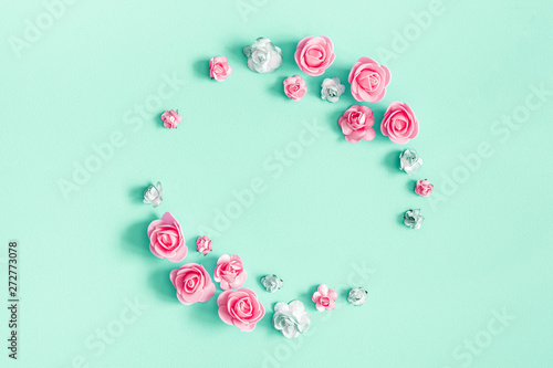 Flowers composition. Frame made of rose flowers on mint background. Flat lay, top view, copy space, square