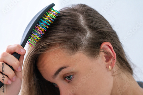 Woman with comb having a hair problem and suffering from hair loss Fototapete