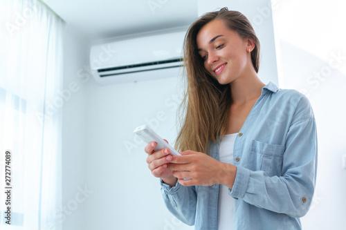 Fotografía  Young attractive woman control air conditioner temperature using remote controller in room at home